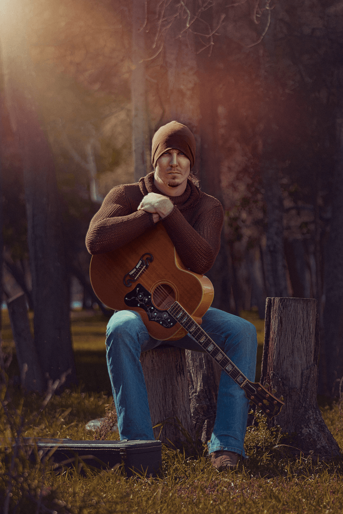 Male Musician with guitar in the woods looking strong by Cowra Photographer Brent Young taken in Sydney NSW